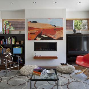 Diseño de biblioteca en casa moderna con paredes blancas, chimenea lineal, marco de chimenea de yeso y pared multimedia