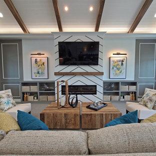 На фото: открытая гостиная комната в стиле современная классика с серыми стенами, ковровым покрытием, стандартным камином, фасадом камина из вагонки, телевизором на стене, серым полом и балками на потолке с