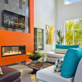Foto di un soggiorno moderno di medie dimensioni e aperto con pareti arancioni, moquette, camino bifacciale, cornice del camino in intonaco, TV a parete e pavimento grigio