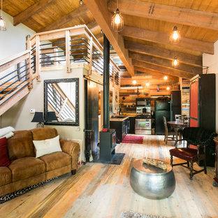Esempio di un piccolo soggiorno stile rurale stile loft con pareti beige, pavimento in legno massello medio, stufa a legna, cornice del camino in metallo e TV a parete