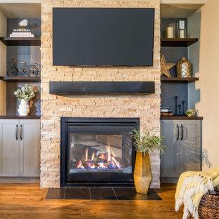 Idée de décoration pour un salon tradition de taille moyenne et ouvert avec un mur beige, un sol en bois brun, une cheminée standard, un manteau de cheminée en pierre de parement, un téléviseur fixé au mur et un sol marron.