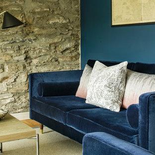 コーンウォールの小さいビーチスタイルのおしゃれなLDK (青い壁、濃色無垢フローリング、薪ストーブ、積石の暖炉まわり、ベージュの床) の写真