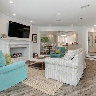 マイアミの大きいビーチスタイルのおしゃれなLDK (白い壁、クッションフロア、標準型暖炉、石材の暖炉まわり、壁掛け型テレビ、茶色い床) の写真