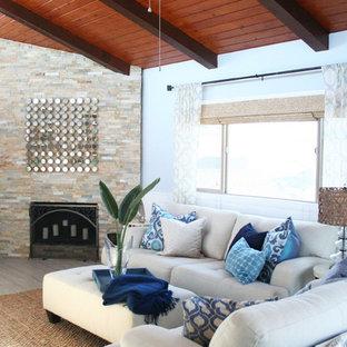 ロサンゼルスの中サイズのビーチスタイルのおしゃれなリビングロフト (青い壁、磁器タイルの床、コーナー設置型暖炉、石材の暖炉まわり、壁掛け型テレビ) の写真
