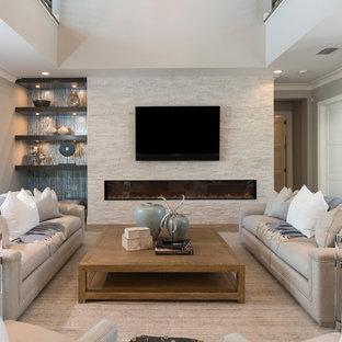 マイアミのビーチスタイルのおしゃれなリビング (グレーの壁、無垢フローリング、コーナー設置型暖炉、石材の暖炉まわり、埋込式メディアウォール、ベージュの床) の写真