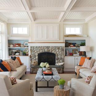 Idee per un soggiorno costiero di medie dimensioni con pareti beige, pavimento in legno massello medio, camino classico, cornice del camino in pietra, TV nascosta e libreria