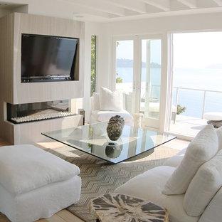 サンフランシスコの大きいビーチスタイルのおしゃれなLDK (フォーマル、白い壁、淡色無垢フローリング、横長型暖炉、木材の暖炉まわり、内蔵型テレビ) の写真