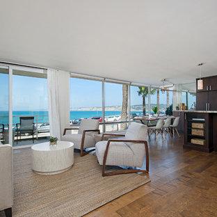 サンディエゴの大きいビーチスタイルのおしゃれなLDK (白い壁、濃色無垢フローリング、据え置き型テレビ、茶色い床) の写真