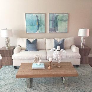 オレンジカウンティの小さいビーチスタイルのおしゃれなLDK (ベージュの壁、無垢フローリング、コーナー設置型暖炉、漆喰の暖炉まわり、据え置き型テレビ) の写真