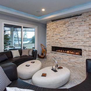 Foto di un soggiorno minimal aperto con pareti grigie, camino lineare Ribbon, cornice del camino in pietra e nessuna TV