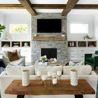 Esempio di un soggiorno stile marinaro di medie dimensioni con pareti bianche, camino classico, cornice del camino in pietra e TV a parete
