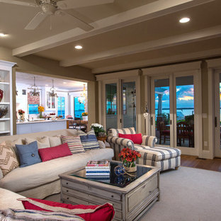 Inspiration for a large beach style enclosed medium tone wood floor living room remodel in Tampa with beige walls, a standard fireplace, a media wall and a brick fireplace