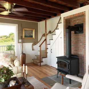 Imagen de salón costero con paredes marrones, suelo de madera en tonos medios y estufa de leña
