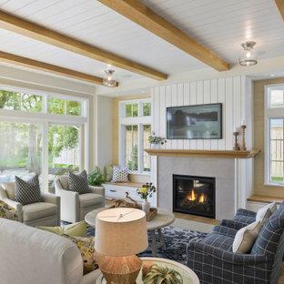 Exempel på ett maritimt vardagsrum, med vita väggar, mellanmörkt trägolv, en standard öppen spis, en väggmonterad TV och brunt golv