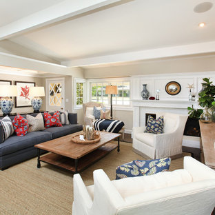Example of a coastal living room design in Orange County with beige walls and a wall-mounted tv