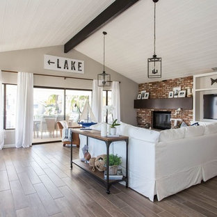 ロサンゼルスの中サイズのビーチスタイルのおしゃれなリビングロフト (ベージュの壁、無垢フローリング、標準型暖炉、レンガの暖炉まわり、壁掛け型テレビ、茶色い床) の写真