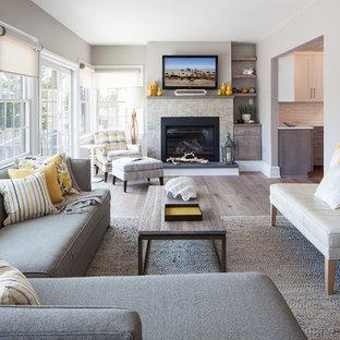 Esempio di un soggiorno design con pareti grigie, pavimento in legno massello medio, camino classico e TV a parete