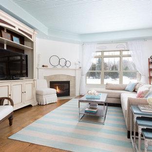 Modelo de salón abierto, marinero, grande, con paredes blancas, suelo de madera en tonos medios, chimenea de esquina, marco de chimenea de baldosas y/o azulejos, televisor independiente y suelo marrón