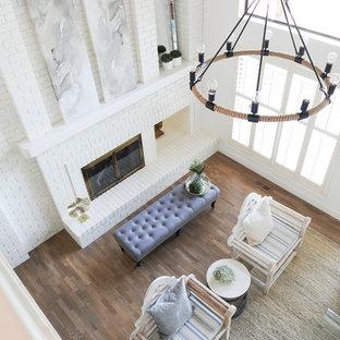 バンクーバーの中くらいのビーチスタイルのおしゃれなリビングロフト (白い壁、淡色無垢フローリング、両方向型暖炉、レンガの暖炉まわり、茶色い床、板張り天井) の写真