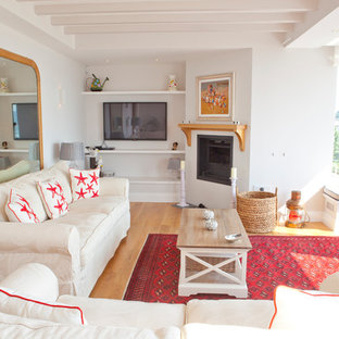 Inspiration for a coastal enclosed living room in Cornwall with white walls, light hardwood flooring, a corner fireplace and a wall mounted tv.
