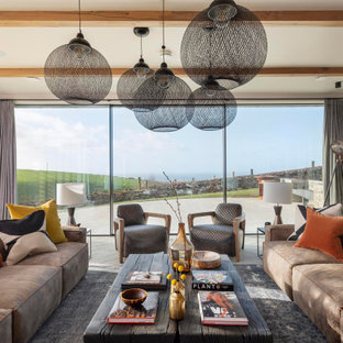 Ejemplo de salón para visitas abierto, costero, grande, con paredes marrones, chimenea de doble cara, marco de chimenea de piedra, pared multimedia y suelo blanco