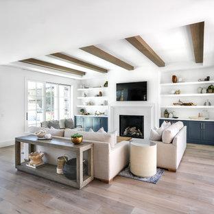 Modern inredning av ett stort allrum med öppen planlösning, med vita väggar, mellanmörkt trägolv, en standard öppen spis, en väggmonterad TV, en spiselkrans i trä och brunt golv