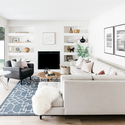 Example of a transitional light wood floor and beige floor living room design in Los Angeles with white walls, a standard fireplace and no tv