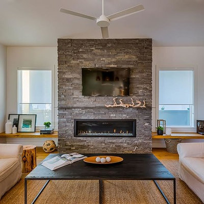 Example of a mid-sized trendy enclosed medium tone wood floor and brown floor living room design in Tampa with white walls, a standard fireplace, a stone fireplace and a wall-mounted tv