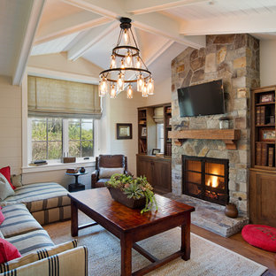 Example of a country living room design in San Diego with beige walls, a standard fireplace and a stone fireplace