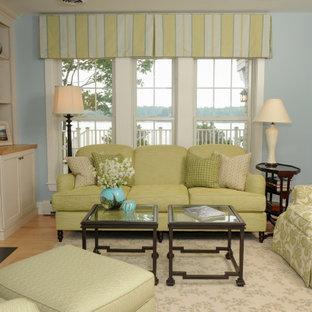 ボストンの中くらいのビーチスタイルのおしゃれなリビング (青い壁、淡色無垢フローリング、標準型暖炉、木材の暖炉まわり、壁掛け型テレビ、オレンジの床) の写真