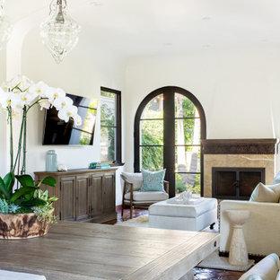 ロサンゼルスの中くらいのビーチスタイルのおしゃれなLDK (白い壁、テラコッタタイルの床、標準型暖炉、石材の暖炉まわり、壁掛け型テレビ、三角天井) の写真