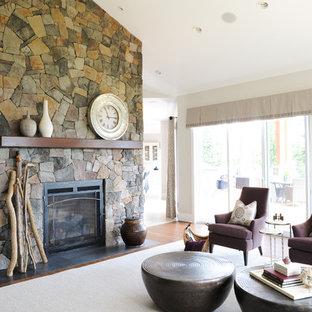 バンクーバーの大きいビーチスタイルのおしゃれなLDK (ベージュの壁、無垢フローリング、標準型暖炉、石材の暖炉まわり、埋込式メディアウォール) の写真