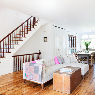 Example of a mid-sized trendy open concept medium tone wood floor and brown floor living room design in New York with white walls