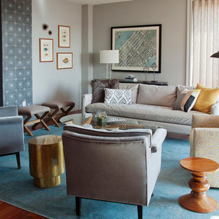 Inspiration for a large transitional loft-style living room in New York with a home bar, grey walls, medium hardwood floors, a two-sided fireplace, a tile fireplace surround, no tv and brown floor.