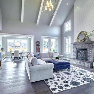 Ispirazione per un soggiorno american style di medie dimensioni e aperto con pareti grigie, parquet scuro, camino classico, cornice del camino in mattoni, nessuna TV e pavimento grigio