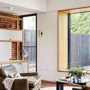 Ejemplo de salón abierto, actual, pequeño, con paredes marrones, televisor retractable, suelo marrón y suelo de madera en tonos medios