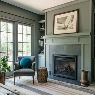 Photo of a traditional living room in Chicago with green walls, light hardwood floors, a standard fireplace and beige floor.