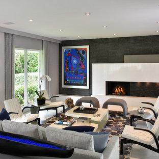 Esempio di un grande soggiorno minimal aperto con sala formale, pareti grigie, pavimento in pietra calcarea e cornice del camino piastrellata