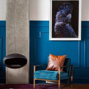 Immagine di un soggiorno minimalista di medie dimensioni e stile loft con sala formale, pareti blu, moquette, camino sospeso, cornice del camino in intonaco, nessuna TV e pavimento marrone