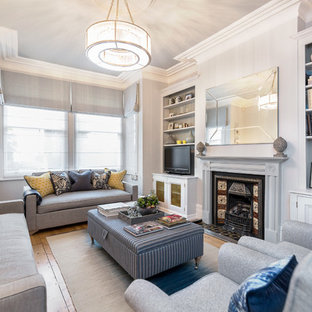 Living room - traditional enclosed medium tone wood floor living room idea in London with gray walls, a wood stove, a tile fireplace and a tv stand