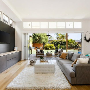 This is an example of a contemporary open concept living room in Sydney with black walls, light hardwood floors, a wall-mounted tv and beige floor.