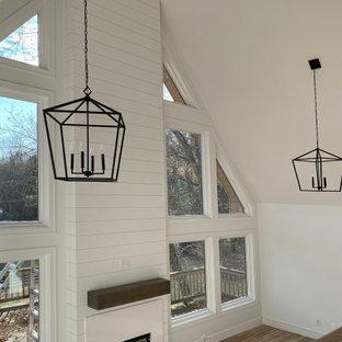 ナッシュビルのトランジショナルスタイルのおしゃれなリビング (淡色無垢フローリング、標準型暖炉、塗装板張りの暖炉まわり、三角天井) の写真