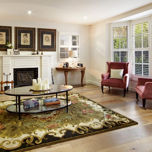 Inspiration for a traditional living room in Melbourne with white walls, medium hardwood floors and a standard fireplace.