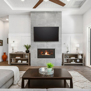 Example of a large minimalist open concept porcelain floor and brown floor living room design in Orlando with gray walls, a standard fireplace, a tile fireplace and a wall-mounted tv