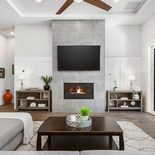 Diseño de salón abierto, minimalista, grande, con paredes grises, suelo de baldosas de porcelana, chimenea tradicional, marco de chimenea de baldosas y/o azulejos, televisor colgado en la pared y suelo marrón
