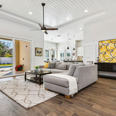 Living room - large modern open concept porcelain tile and brown floor living room idea in Orlando with gray walls, a standard fireplace, a tile fireplace and a wall-mounted tv