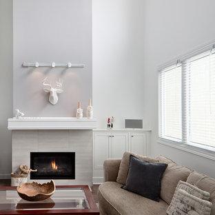 トロントの広いコンテンポラリースタイルのおしゃれな独立型リビング (グレーの壁、ラミネートの床、標準型暖炉、タイルの暖炉まわり) の写真