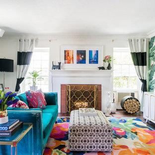 Idee per un soggiorno tropicale con pareti multicolore, parquet scuro, camino classico, cornice del camino in mattoni, TV a parete e pavimento marrone