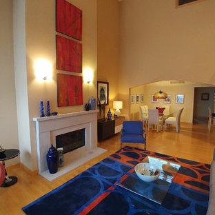 Foto de salón tipo loft, ecléctico, grande, con paredes beige, suelo de madera clara, chimenea tradicional, marco de chimenea de hormigón y suelo beige