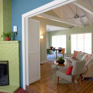 Immagine di un soggiorno stile marinaro di medie dimensioni con pareti verdi, pavimento in legno massello medio, camino ad angolo e cornice del camino in mattoni